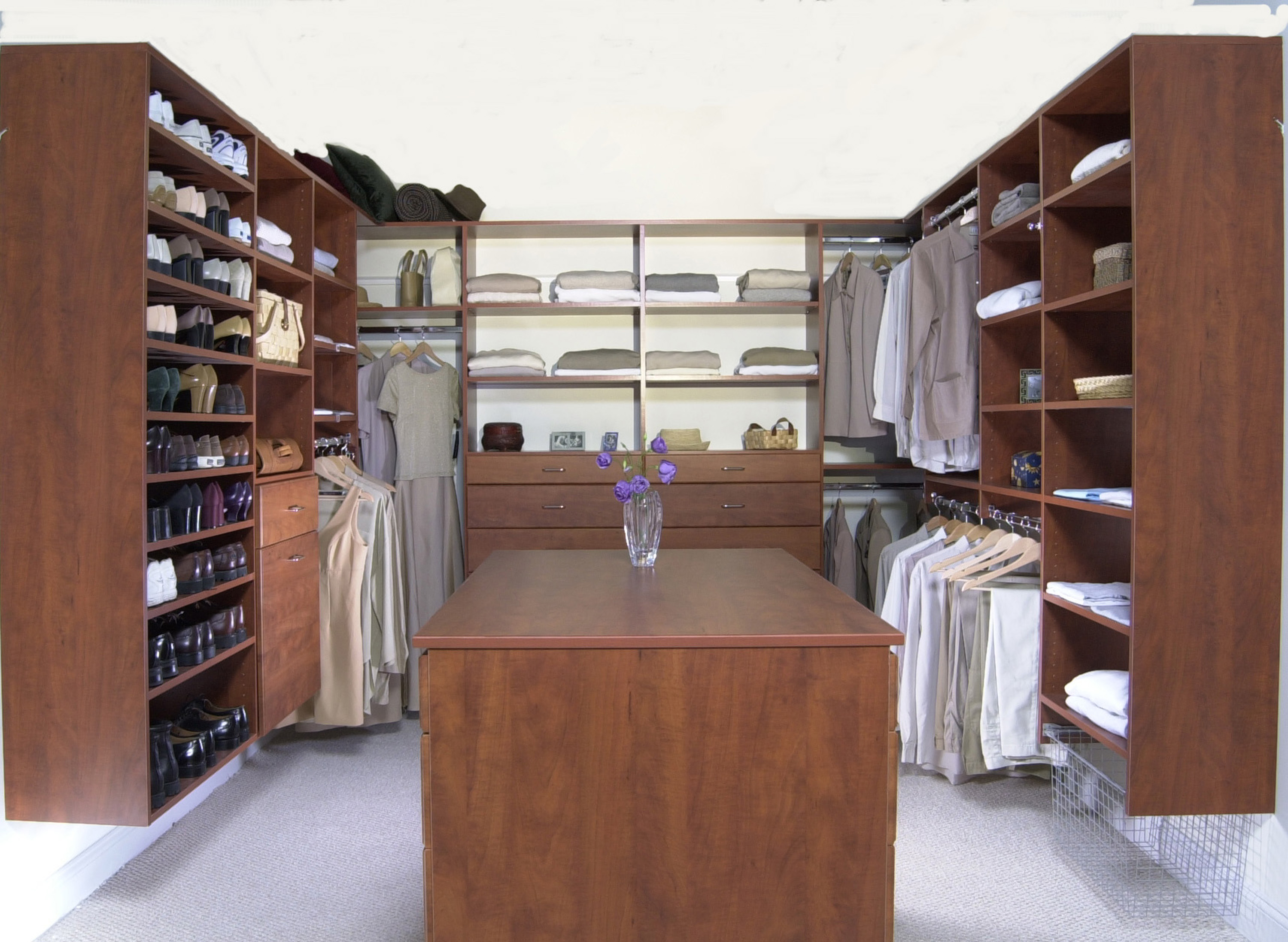 Large walk-in closet with center island and wire laundry basket, in a  cherry finish